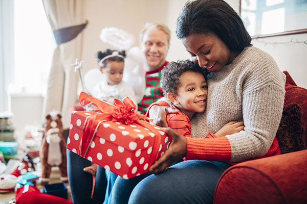 young boy and his mother opening Christmas gifts during the holidays with their family