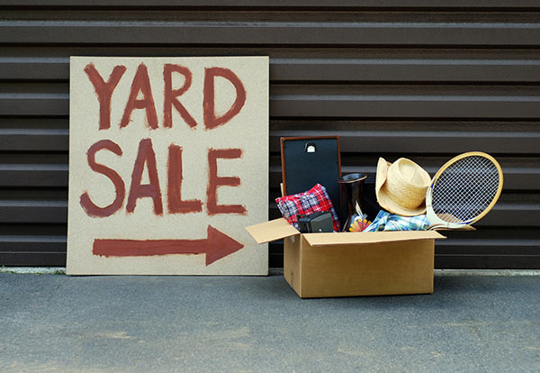 yard sale sign next to a pile of items to sell