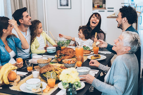 Family laughing and enjoying Thanksgiving Day Dinner.